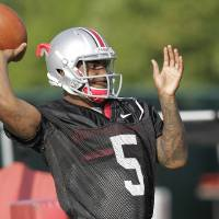 Photo - FILE - In this Aug. 9, 2014, file photo, Ohio State quarterback Braxton Miller warms up during an NCAA college football practice, in Columbus, Ohio. Miller, among the top contenders for the Heisman Trophy, reportedly reinjured his throwing shoulder during practice. The report about the two-time Big Ten offensive player of the year comes with just more than two weeks before the No. 5 Buckeyes open the season. (AP Photo/Jay LaPrete, File)