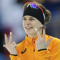 Photo - Ireen Wust of the Netherlands flashes three fingers in each hand, indicating her third olympic gold medal, after winning gold in the women's 3,000-meter speedskating race at the Adler Arena Skating Center during the 2014 Winter Olympics, Sunday, Feb. 9, 2014, in Sochi, Russia.  (AP Photo/Matt Dunham)