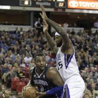 Photo - Orlando Magic center Glen Davis, left, goes to the basket against Sacramento Kings center DeMarcus Cousins during the first quarter of an NBA basketball game in Sacramento, Calif., Friday, Jan. 10, 2014. (AP Photo/Rich Pedroncelli)