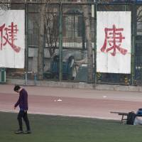 Photo - In this Saturday, Jan. 19, 2013 photo. a college student kicks a soccer ball in front of Chinese characters on the fence reading
