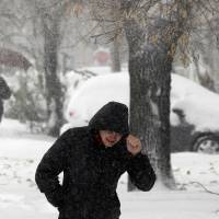 Photo - People walk through the snow covered street during the snow storm in Belgrade, Serbia, Sunday, Dec. 9, 2012. Freezing temperatures and heavy snowfall have killed at least 5 people and caused travel chaos across the Balkans. (AP Photo/Darko Vojinovic)