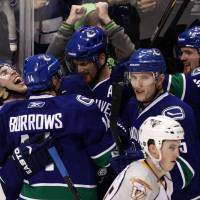 Photo -   Vancouver Canucks' Lee Sweatt, left, celebrates after scoring his first NHL goal with teammates, ffrom left of Sweatt, Alex Burrows, Daniel Sedin, of Sweden, Christian Ehrhoff, of Germany, and Henrik Sedin, of Sweden, as Nashville Predators' Jerred Smithson, lower right, skates past during the third period of an NHL hockey game in Vancouver, British Columbia, Wednesday Jan. 26, 2011. (AP Photo/THE CANADIAN PRESS/Darryl Dyck)