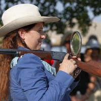 Photo - Marna Davis portrays Old West sharpshooter and trick shot expert Annie Oakley. Davis is from Hitchcock. Here, she is demonstrating a trick shot by shooting a rifle balanced on her shoulder and looking into a mirror to see the target.