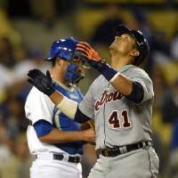 Photo - Detroit Tigers' Victor Martinez, right, looks to the sky after hitting a solo home run as Los Angeles Dodgers catcher Drew Butera looks on during the 10th inning of a baseball game, Wednesday, April 9, 2014, in Los Angeles. (AP Photo/Mark J. Terrill)
