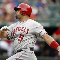 Photo - Los Angeles Angels' Albert Pujols follows through on his solo home run against the Texas Rangers during the first inning of a baseball game, Saturday, Aug. 16, 2014, in Arlington, Texas. (AP Photo/Jim Cowsert)