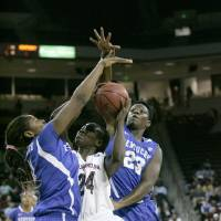 Photo - South Carolina's Aleighsa Welch (24) drives for the basket as Kentucky's Samarie Walker (23) and DeNesha Stallworth (11) tries to block during the first half of their NCAA college basketball game Thursday Jan. 9, 2014, in Columbia, S.C. (AP Photo/Mary Ann Chastain)