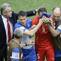 Photo - Switzerland's coach Ottmar Hitzfeld, left, comforts his injured player Steve von Bergen, second right, during the group E World Cup soccer match between Switzerland and France at the Arena Fonte Nova in Salvador, Brazil, Friday, June 20, 2014. (AP Photo/Sergei Grits)
