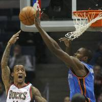 Photo - Milwaukee Bucks' Monta Ellis, left, has his shot blocked by Oklahoma City Thunders' Serge Ibaka during the first half of an NBA basketball game Monday, April 9, 2012, in Milwaukee. (AP Photo/Jeffrey Phelps)  ORG XMIT: WIJP107  JEFFREY PHELPS - AP