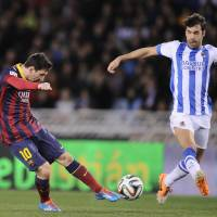 Photo - FC Barcelona's Lionel Messi of Argentina, left, kicks the ball in front Real Sociedad's Xabier Prieto, during their Spanish Copa del Rey semifinal second leg soccer match, at Anoeta stadium, in San Sebastian northern Spain, Wednesday, Feb. 12, 2014. (AP Photo/Alvaro Barrientos)