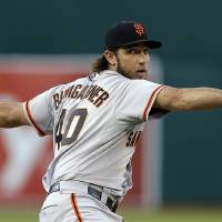 Photo - San Francisco Giants' Madison Bumgarner works against the Oakland Athletics in the first inning of a baseball game Tuesday, July 8, 2014, in Oakland, Calif. (AP Photo/Ben Margot)