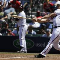 Photo - Atlanta Braves' Evan Gattis doubles to score teammates Ramiro Pena and Dan Uggla in the eighth inning of a baseball game against the Miami Marlins, Wednesday, April 23, 2014, in Atlanta. The Braves won 3-1. (AP Photo/David Goldman)
