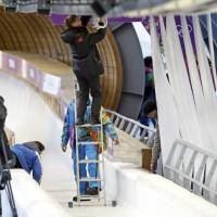 Photo - A track worker repairs some lights that were damaged after a worker was hit by a forerunner bobsled just before the men's two-man bobsled training at the 2014 Winter Olympics, Thursday, Feb. 13, 2014, in Krasnaya Polyana, Russia. (AP Photo/Dita Alangkara)