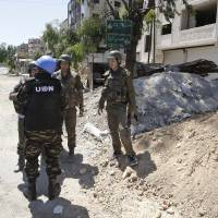 Photo -   Syrian government forces speak to a U.N. observer in the Damascus suburb of Douma, Syria, Sunday, May 20, 2012. A roadside bomb exploded in a restive suburb of the Syrian capital as senior U.N. officials toured the area on Sunday, the latest incident in which the unarmed observer mission has nearly been caught up in the country's bloodshed. (AP Photo/Muzaffar Salman)