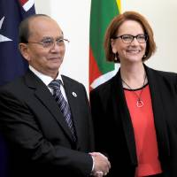 Photo - President of Myanmar Thein Sein, left, shakes hands with Australian Prime Minister Julia Gillard as they meet at Parliament House in Canberra, Australia, Monday, March 18, 2013. Thein is on a three day visit to Australia.  (AP Photo/Alan Porritt, Pool)