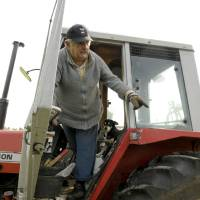 Photo - FILE - In this Oct. 25, 2009, file photo Uruguay's President Jose Mujica, 74, stands in a tractor on his flower farm on the outskirts of Montevideo, Uruguay, Sunday. While outside his country he is an international figure, well known for his modest lifestyle, consistent with his ideals and his good-nature, among his own people Uruguay's  President known as