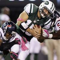Photo -   New York Jets quarterback Tim Tebow (15) is tackled by Houston Texans strong safety Glover Quin (29) and inside linebacker Bradie James (53) during the first half of an NFL football game, Monday, Oct. 8, 2012, in East Rutherford, N.J. (AP Photo/Kathy Willens)