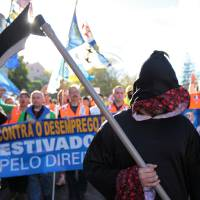 Photo - Dockworkers arrive outside the Portuguese parliament in Lisbon Thursday, Nov. 29 2012, during a protest by several European dockworkers unions. In the parliament lawmakers were debating a new law that the worker's claim will lead to the loss of jobs. (AP Photo/Armando Franca)
