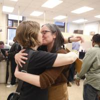 Photo - Emily Gavin and Eliza Callard kiss after getting their marriage license this morning at the Register of Wills at City Hall in Philadelphia on Wednesday, May 21, 2014.  Same-sex couples in Pennsylvania clamored for marriage licenses after a judge ruled to allow the state to join the rest of the Northeast in legalizing gay weddings, with Philadelphia offices staying open late to handle a rush of applications. Under state law, couples must wait three days after their application to get married unless a sympathetic judge grants a waiver.  (AP Photo/The Philadelphia Inquirer, Ed Hille)