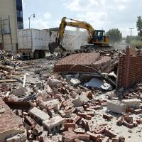 Photo - A wrecking crew works on demolishing a city-owned building at Gray Street and Peters Avenue.  PHOTO BY STEVE SISNEY, THE OKLAHOMAN