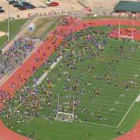 Photo - In this image from video provided by KHOU, students evacuated from Seven Lakes High School in Katy, Texas, mingle on the football field on Monday Jan. 13, 2014 after officials say a