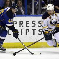 Photo - Buffalo Sabres' Cody Hodgson, right, and St. Louis Blues' Maxim Lapierre chase after a loose puck during the first period of an NHL hockey game on Thursday, April 3, 2014, in St. Louis. (AP Photo/Jeff Roberson)
