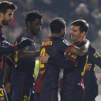 Photo - Barcelona's Lionel Messi, right, celebrates with teammates Daniel Alves, second right, Alexandre Song, second left, and Gerard Pique, left, after scoring against Cordoba during the 1st leg of a last-16 Copa del Rey soccer match  at Arcangel stadium in, Cordoba, Spain on Wednesday, Dec. 12, 2012. (AP Photo/Angel Fernandez)