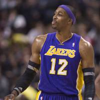 Photo - Los Angeles Lakers forward Dwight Howard, right, looks at the referee after being ejected from the game while playing against the Toronto Raptors during first half NBA basketball action in Toronto on Sunday Jan. 20, 2013. (AP Photo/THE CANADIAN PRESS,Nathan Denette)