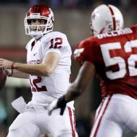 Photo - Oklahoma's Landry Jones (12) looks to throw the ball against the Nebraska defense during the first half of the college football game between the University of Oklahoma Sooners (OU) and the University of Nebraska Cornhuskers (NU) on Saturday, Nov. 7, 2009, in Lincoln, Neb.  Photo by Chris Landsberger, The Oklahoman ORG XMIT: KOD
