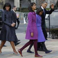 Photo - President Barack Obama, waves as he walks with his daughters Sasha and Malia, first lady Michelle Obama and mother-in-law Marian Robinson, to St. John's Church in Washington, Monday, Jan. 21, 2013, for a church service during the 57th Presidential Inauguration. (AP Photo/Jacquelyn Martin)