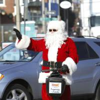 Photo - The Sonic Segway Santa waves to visitors in Bricktown in Oklahoma City, Friday December 13, 2013. Photo By Steve Gooch, The Oklahoman