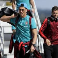 Photo - Portugal's soccer players Cristiano Ronaldo, foreground, with Miguel Veloso, centre, and Raul Meireles behind, walk down from a plane as they arrive at the Viracopos airport, in Campinas, Brazil, Tuesday, June 11, 2014. Portugal will play in group G of Brazil's 2014 soccer World Cup. (AP Photo/Paulo Duarte)