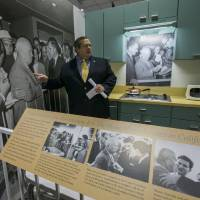 Photo - In this Tuesday, Feb. 12, 2013 photo, curator Bob Bostock, a former Richard Nixon aide who designed the original Watergate exhibit, points at the famous Soviet Premier Nikita Khrushchev picture, inside a re-creation of the 1950s-era modern American kitchen exhibited in Moscow where Nixon and Khrushchev had their fiery exchange debating the merits of freedom versus communism, on display at the Richard Nixon Presidential Library and Museum in Yorba Linda, Calif. (AP Photo/Damian Dovarganes)