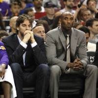 Photo -   Dressed in street clothes, Los Angeles Lakers' Pau Gasol, left, of Spain, and Kobe Bryant watch the first half an NBA basketball game against the Sacramento Kings in Sacramento, Calif., Thursday, April 26, 2012. (AP Photo/Rich Pedroncelli)