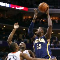 Photo - Indiana Pacers' Roy Hibbert (55) shoots over Charlotte Bobcats' Kemba Walker (15) and Bismack Biyombo (0) during the first half of an NBA basketball game in Charlotte, N.C., Tuesday, Jan. 15, 2013. (AP Photo/Chuck Burton)