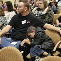 Photo - Xizavier (cq) Molden, 5, takes a nap in a chair while his mother, Kathryn Molden, not shown, and other child care providers attend meeting with state regulators.  Seated next to the boy is David Beasley, with Children's Lighthouse 3. About 200  child care providers attended a public forum at Francis Tuttle Technology Center, Reno campus, to  voice their concerns with DHS regulators during a 2-hour session Tuesday afternoon, Nov. 27, 2012.  Photo by Jim Beckel, The Oklahoman