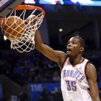 Photo - Oklahoma City Thunder forward Kevin Durant dunks  against the Golden State Warriors in the second quarter of an NBA basketball game in Oklahoma City, Sunday, Dec. 5, 2010. Durant had 28 points as Oklahoma City won 114-109. (AP Photo/Sue Ogrocki)