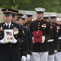 Photo - Honor guard members carry the remains of Army Pvt Lycurgus McCormack, a Civil War veteran, in white urn, Marine Pfc. Albert Klatt, a WWII veteran, in red urn, and  Navy Seaman 2nd Class Peter Schwartz, during committal services at Arlington National Cemetery on Thursday, May 9, 2013 in Arlington, Va.  Arlington National Cemetery dedicated its ninth columbarium court by conducting a joint full honors committal service for six unclaimed remains of veterans from all branches of the Armed Forces. (AP Photo/Kevin Wolf)