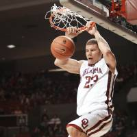 Photo - OU: University of Oklahoma's Blake Griffin dunks in front of American's Jordan Nichols, left, in the second half of an NCAA men's college basketball game in Norman, Okla., Friday, Nov. 14, 2008. Blake Griffin had 24 points as Oklahoma defeated American 83-54. (AP Photo/Sue Ogrocki) ORG XMIT: OKSO110