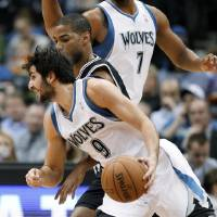 Photo - Minnesota Timberwolves guard Ricky Rubio (9), of Spain, drives around San Antonio Spurs guard Gary Neal during the first half of an NBA basketball game Wednesday, Feb. 6, 2013, in Minneapolis. (AP Photo/Genevieve Ross)