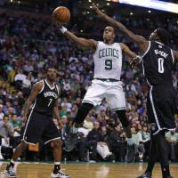 Photo - Boston Celtics guard Rajon Rondo (9) drives to the basket between Brooklyn Nets guards Deron Williams (8) and Joe Johnson (7) during the second quarter of an NBA basketball game, Friday, March 7, 2014, in Boston. (AP Photo/Charles Krupa)