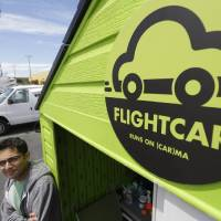 Photo - In this photo taken Tuesday, June 11, 2013 Flightcar CEO Rujul Zaparde, poses outside a small rental shack on their lot in Burlingame, Calif. A San Francisco Bay area startup company founded by three teenage Ivy League dropouts is trying to change the airport car rental business. FlightCar rents out people's personal vehicles while they are traveling, giving them a share of the proceeds and free airport parking in exchange. But the company's rosy outlook does have some thorns. San Francisco's City Attorney has sued FlightCar, accusing it of unfair competition. (AP Photo/Eric Risberg)