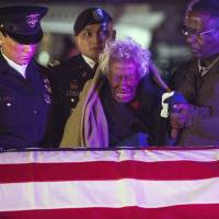 Photo - Clara Gantt, the 94-year-old widow of U.S. Army Sgt. Joseph Gantt, weeps in front of her her husband's casket after it was lowered from the plane, Friday, Dec. 20, 2013 in Los Angeles. Sixty-three years after Army Sgt. 1st Class Joseph E. Gantt went missing in action during the Korean War, his remains were returned to his 94-year-old widow in a solemn ceremony at Los Angeles International Airport before dawn Friday.  (AP Photo/Los Angeles Times, Andrew Renneisen, Pool)