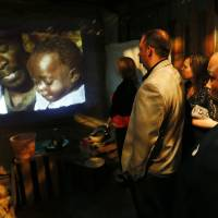 Photo - People watch a film about the conditions in the slums of Kenya during the opening of the