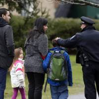 Photo - Easton police officer J. Sollazzo greets a returning student as he is walked into Hawley School in Newtown, Conn., Tuesday, Dec. 18, 2012. Classes resumed Tuesday for Newtown, schools except those at Sandy Hook, following Friday's mass shooting at the Sandy Hook Elementary School. Buses ferrying students to schools were festooned with large green and white ribbons on the front grills, the colors of Sandy Hook. At Newtown High School, students in sweatshirts and jackets, many wearing headphones, betrayed mixed emotions. (AP Photo/Jason DeCrow)