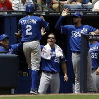 Photo - Kansas City Royals' Alcides Escobar (2) is high-fived by manager Ned Yost, left, and teammates George Kottaras (26) and James Shields, right, after scoring off a single by Jeff Francoeur, not pictured, in the fourth inning of a baseball game against the Atlanta Braves, Wednesday, April 17, 2013, in Atlanta. (AP Photo/David Goldman)