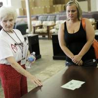 Photo - Nola Schuermann helps Amanda Swann of Moore pick out furniture at the Furniture Bank of Oklahoma on July 6, 2013.  The furniture bank is operated by members of the First Baptist Church of Oklahoma City. Photo by KT KING, The Oklahoman