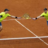 Photo - USA's Bob, left, and Mike Bryan return the ball to Spain's Marcel Granollers and Marc Lopez during their quarterfinal match of  the French Open tennis tournament at the Roland Garros stadium, in Paris, France, Monday, June 2, 2014. The Spanish pair won 6-4, 6-2. (AP Photo/Darko Vojinovic)