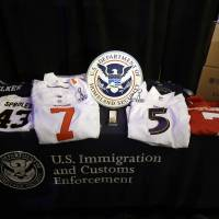 Photo - Confiscated counterfeit merchandise is displayed at a news conference regarding counterfeit NFL football merchandise and tickets for the upcoming Super Bowl XLVII in New Orleans, Thursday, Jan. 31, 2013. (AP Photo/Gerald Herbert)