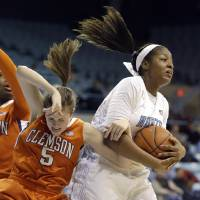 Photo - North Carolina's Stephanie Mavunga, right, and  Clemson's Kelly Gramlich (5) struggle for possession of the ball during the first half of an NCAA college basketball game in Chapel Hill, N.C., Thursday, Jan. 16, 2014. (AP Photo/Gerry Broome)