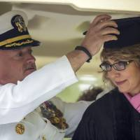 Photo - Former U.S. Rep. Gabrielle Giffords leans forward as her husband, Mark Kelly, retired space shuttle commander, adjusts her mortarboard as they ride in the procession for the 153rd Commencement at Bard College, Saturday, May 25, 2013, in Annandale-on-Hudson, N.Y. They delivered the commencement address, and Giffords received an honorary degree. (AP Photo/Philip Kamrass)